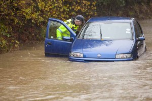 PC Paul Burke inspects a flooded car form ocupants on the outskirts of Ambleside.