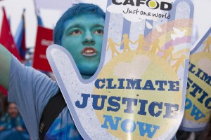 A protestor at The Wave demands climate justice.