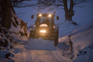 A farmer clearing snow from a track above Ambleside, Cumbria, UK.