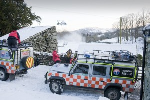 Langdale Ambleside mountain Rescue team members and the North West Air Ambulance evacuate an injured walker who had fallen in the snow, Langdale, UK.