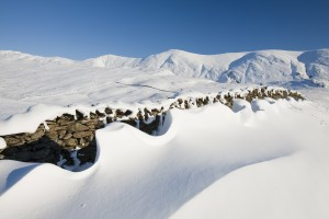 Snow drifts on the side of Kirkstone Pass which has been closed for weeks, Lake District, UK.