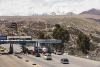 South-America;Bolivia;La-Paz;city;house;housing;dense;density;slope;hilly;Andes;altitude;high;infrastructure;overcrowded;population;building;buildings;road;highway;toll;toll-booth;traffic;taxi;mountain;snow;glacier;glacial-retreat;backdrop;Huayna-Potosi;Altiplano;mountain-range;Cordillera-Real