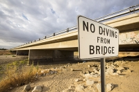 USA;US;America;California;brown;drought;dessicated;dried-up;climate-change;global-warming;parched;Kern-County;Kern-River;river-bed;burnt;Bakersfield;bridge;road;crossing;sign;composite;no-jumping;jumping
