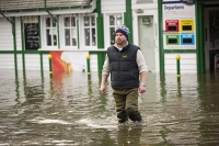 Floods;flooding;flooded;Ambleside;Cumbria;Lake-District;UK;weather;extreme-weather;climate-change;global-warming;deluge;torrential-rain;downpour;meteorology;low-pressure;weather-front;rain;raining;heavy-rain;precipitation;wet;sodden;surrounded;marooned;insuramnce;insurance-claim;man;wade;waders;pier;Ambleside-Pier;jetty