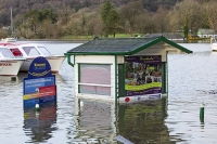 Floods;flooding;flooded;Ambleside;Cumbria;Lake-District;UK;weather;extreme-weather;climate-change;global-warming;deluge;torrential-rain;downpour;meteorology;low-pressure;weather-front;rain;raining;heavy-rain;precipitation;wet;sodden;surrounded;marooned;insuramnce;insurance-claim;man;wade;waders;pier;Ambleside-Pier;jetty;cabin;hut;inundated