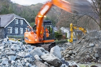 Floods;flooding;flooded;Glenridding;Ullswater;Cumbria;Lake-District;UK;weather;extreme-weather;climate-change;global-warming;deluge;torrential-rain;downpour;meteorology;low-pressure;weather-front;rain;raining;heavy-rain;precipitation;wet;sodden;flood-waters;tarmac;flood-damage;ripped-up;debris;flood-debris;village;fridge;storm-Desmond;workman;high-vis;clearup;cleanup;pumping;pumping-out;road;destroyed;destruction;river;JCB;digger;plant;machinery;clearing;river;orange