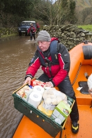 Floods;flooding;flooded;Glenridding;Ullswater;Cumbria;Lake-District;UK;weather;extreme-weather;climate-change;global-warming;deluge;torrential-rain;downpour;meteorology;low-pressure;weather-front;rain;raining;heavy-rain;precipitation;wet;sodden;flood-waters;tarmac;flood-damage;storm-Desmond;Land-Rover;emergency-services;mountain-rescue-mountain-rescue-team;Patterdale-Mountain-Rescue-Team;relief;volunteer;volunteers;relief-work;boat;rib;inflateable;launch;launching;orange;outboard;outboard-motor;man;male;food;food-relief;food-supplies;lake;Ullswater;speed;helmet;PPE