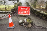 Floods;flooding;flooded;Cumbria;Lake-District;UK;Ambleside;weather;extreme-weather;climate-change;global-warming;deluge;torrential-rain;downpour;meteorology;low-pressure;weather-front;rain;raining;heavy-rain;precipitation;flood-waters;river;swept-away;undermined;flood-damage;power;destroyed;destruction;flood-damage;ripped-apart;River-Rothay;stone;collapsed;infrastructure;eroded;erosion;closed;road-closed;inconvenience;hole;parapet;scour;scoured;bridge;bridge-closure;closed;Rothay-park;red;yellow;road-sign