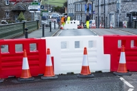 Floods;flooding;flooded;Cumbria;Lake-District;UK;Kendal;weather;extreme-weather;climate-change;global-warming;river;undermined;flood-damage;power;River-Kent;crossing;shut;infrastructure;man;male;inspection;engineer;Victoria-Bridge;workman;traffic-cone;barrier;red;colourful