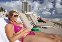 America;USA;Florida;Miami;beach;coast;ocean;sea;Atlantic;Atlantic-Ocean;Miami-Beach;morning;wave;shore;blue;light;real-estate;tower;tower-block;apartment;hotel;expensive;oceanfront;vulnerable;sea-level-rise;woman;body;suntan;sunbathing;female;bikini;sexy;good-looking;attractive;slim;pink;lounger;sun-lounger;sun-bed;relax;relaxing;reclining;sunglasses;phone;cell-phone;mobile-phone;connected