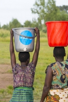 Malawi;Africa;Chiteskesa;refugee-camp;flood;floods;flooding;displaced;charity;NGO;aid;female;woman;black;African;green;dress;women;disaster;disaster-relief;climate-change;global-warming;refugee;poor;poverty;bucket;plastic;carry;carrying;water;head;carrying-on-your-head;balance;balancing