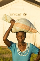 Malawi;Africa;Chiteskesa;refugee-camp;flood;floods;flooding;displaced;charity;NGO;aid;female;woman;black;African;green;dress;women;disaster;disaster-relief;climate-change;global-warming;refugee;poor;poverty;mother;child;Unicef;World-Food-Program;sack;food;food-supply;balance;carry;carrying