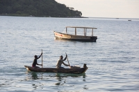 Malawi;Africa;Lake-Malawi;Cape-Maclear;sunlight;tropics;boat;tranquil;peaceful;water;man;male;Black;African;canoe;dug-out-canoe;traditional;fishing;fisherman;paddle;paddling;lake-fish