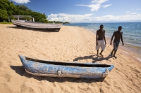 Malawi;Africa;Lake-Malawi;Cape-Maclear;sunlight;tropics;boat;tranquil;peaceful;water;man;male;Black;African;canoe;dug-out-canoe;traditional;fishing;fisherman;blue;beach;sand;sandy;sandy-beach