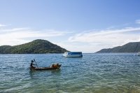Malawi;Africa;Lake-Malawi;Cape-Maclear;sunlight;tropics;boat;tranquil;peaceful;water;canoe;dug-out-canoe;traditional;blue;beach;sand;sandy;sandy-beach;fishing;man;male;paddle;paddling;fisherman