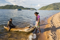 Malawi;Africa;Lake-Malawi;Cape-Maclear;sunlight;tropics;boat;tranquil;peaceful;water;canoe;dug-out-canoe;traditional;blue;beach;sand;sandy;sandy-beach;fishing;man;male;paddle;paddling;fisherman;woman