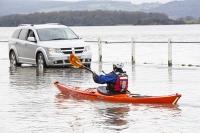 sea;sea-front;promenade;damage;destruction;storm-damage;Irish-sea;climate-change;global-warming;shingle;seafront;High-Street;power;powerful;weather;extreme-weather;storm-surge;infrastructure;road;flooded-road;Sandside;Storth;Arnside;Kent-estuary;Morecambe-Bay;high-tide;flood-waters;inundated;salt-water;tidal;tidal-surge;pedestrian;onlooker;observer;canoe;canoeist;kayak;kayaker;kayaking;paddle;paddling;sign;road-sign;orange;man;male;car;driver;stranded;stuck