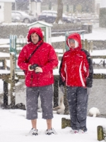 snow;Ambleside;Cumbria;UK;snowing;weather;ornithology;lake;Windermere;colourful;lake-shore;couple;man;woman;male;female;red;camera;photography;snow-storm;snow-shower;jetty