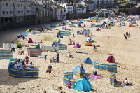St-Ives;Cornwall;UK;coast;sea;shallow;summer;holiday;town;boat;craft;sky;blue;sun;sunny;bright;house;housing;shop;seafront;promenade;colourful;red;yellow;beach;sand;crowd;relaxing;summer-holiday;tourist;tourism;beach-holiday;wind-break;shelter;crowds;people;family