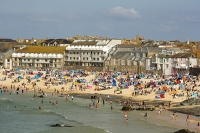 St-Ives;harbour;high-tide;Cornwall;UK;coast;sea;shallow;summer;holiday;town;boat;craft;sky;blue;sun;sunny;bright;house;housing;shop;seafront;promenade;colourful;red;yellow;beach;sand;crowd;relaxing;summer-holiday;tourist;tourism;beach-holiday;wind-break;shelter;crowds;people;family;surfer;surfing;surf-board