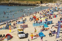 St-Ives;harbour;high-tide;Cornwall;UK;coast;sea;shallow;summer;holiday;town;boat;craft;sky;blue;sun;sunny;bright;house;housing;shop;seafront;promenade;colourful;red;yellow;beach;sand;crowd;relaxing;summer-holiday;tourist;tourism;beach-holiday;wind-break;shelter;crowds;people;family;surfer;surfing;surf-board;RNLI;life-saving;crowded;crowds