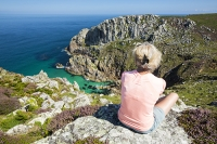 Zennor;Cornwall;UK;coast;sea;Atlantic-ocean;headland;edge;moor;moorland;heather;flower;flowering;pink;heather;ling;Calluna-vulgaris;summer;August;blooming;flowering;carpet;sea-cliff;vegetation;flora;bay;inlet;sea-cliff;turquoise;aquamarine;promontary;landscape;colourful;cliff;sea-cliff;crag;Granite;Igneous;weathering;erosion;coastal-erosion;Bosigran;woman;female;sit;sitting;middle-aged;50s;fifties;coastal-walking;South-West-Coast-Path;view-point