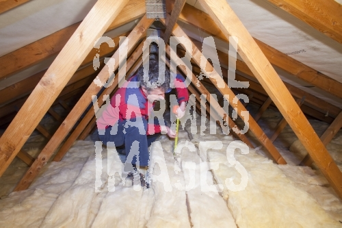 A man measuring the depth of insulation in a house loft or roof space. Insulating your loft can save a significant amount of household heat loss and therefore help save energy and help combat climate change