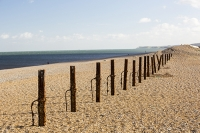 cley;Norfolk;UK;North-Norfolk;coast;tidal;beach;shingle;flint;cobble;damage;flood-surge;storm-surge;person;walker;walking;breach;breached;storm-beach;inundated;wildlife-reserve;bird-reserve;rust;rusty;rusting;second-world-war;defences;post;iron;metal