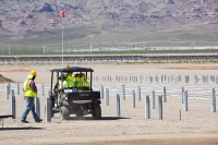 USA;US;America;Nevada;desert;electricity;generating;renewable;renewable-energy;solar;solar-power;solar-panel;PV;photo-voltic;South;aspect;south-facing;carbon-neutral;climate-change;global-warming;sign;Copper-Mountain;copper-mountain-solar;investment;clean-energy;technology;construction;green;green-energy;construction-work;engineering;flat;valley-floor;man;male;construction-worker;worker;PPE;hard-hat;helmet;orange;high-vis;heat;hot;sun;sunlight;sunstroke;shelter;protection;shade;rest;rest-break;vehicle;buggy;transport