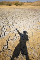 USA;US;America;California;brown;drought;dessicated;dried-up;climate-change;global-warming;parched;Kern-County;Bakersfield;Central-Valley;water-crisis;water-shortage;dust;dust-bowl;desperate;lake;wildlife-reserve;bird-reserve;Kern-Vslley-Wildlife-refuge;empty;lake-bed;gras;browned-off;burnt;mud-cracks;shadow;shade;man;male;photographer;Ashley-Cooper