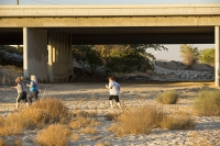 USA;US;America;California;brown;drought;dessicated;dried-up;climate-change;global-warming;parched;Kern-County;Kern-River;river-bed;burnt;Bakersfield;sand;sandy;concrete;bridge;crossing;road;highway;support;column;light;glow;dusk;sunset;orange;woman;female;runner;running;run;jogger;fat;obesity;overweight