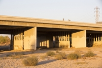 USA;US;America;California;brown;drought;dessicated;dried-up;climate-change;global-warming;parched;Kern-County;Kern-River;river-bed;burnt;Bakersfield;sand;sandy;concrete;bridge;crossing;road;highway;support;column;light;glow;dusk;sunset;orange