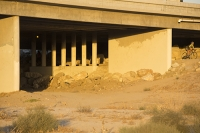 USA;US;America;California;brown;drought;dessicated;dried-up;climate-change;global-warming;parched;Kern-County;Kern-River;river-bed;burnt;Bakersfield;sand;sandy;concrete;bridge;crossing;road;highway;support;column;light;glow;dusk;sunset;orange;cyclist