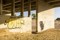 USA;US;America;California;brown;drought;dessicated;dried-up;climate-change;global-warming;parched;Kern-County;Kern-River;river-bed;burnt;Bakersfield;sand;sandy;concrete;bridge;crossing;road;highway;support;column;graffiti;art;glow;sunset;light