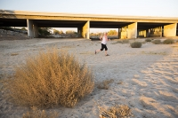 USA;US;America;California;brown;drought;dessicated;dried-up;climate-change;global-warming;parched;Kern-County;Kern-River;river-bed;burnt;Bakersfield;sand;sandy;concrete;bridge;crossing;road;highway;support;column;woman;run;runner;running;jogger