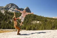 USA;US;America;California;tourist-attraction;light;sunlight;Yosemite-National-Park;Autumn;Fall;tree;mountain;forest;granite;rock;batholith;geology;weathering;erosion;igneous;dome;man;male;young;twentys;performer;performance;art;skill;balance;strength;agility;lift;lifting;circus-act;athlete;athletic;muscles;muscle-strength;grace;poise;hold;trust;trusting;backdrop