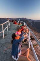 USA;US;America;California;tourist-attraction;light;sunlight;Sequoia-National-Park;mountain;granite;Moro-Rock;outcrop;lichen;erosion;weathering;peak;viewpoint;vista;steps;fence;tourists;summit;railings;fence;backdrop;couple;young-women;tranquil;dusk;sunset;light;glow;warm;wilderness;escape;nature;experience;sunglasses;firend;friends;glowing;pink;orange;red;sky;phone;mobile-phone;cell-phone