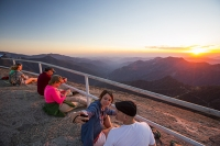 USA;US;America;California;tourist-attraction;light;sunlight;Sequoia-National-Park;mountain;granite;Moro-Rock;outcrop;lichen;erosion;weathering;peak;viewpoint;vista;steps;fence;tourists;summit;railings;fence;backdrop;couple;young-women;tranquil;dusk;sunset;light;glow;warm;wilderness;escape;nature;experience;sunglasses;firend;friends;glowing;pink;orange;red;sky;selfi;selfy
