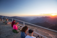 USA;US;America;California;tourist-attraction;light;sunlight;Sequoia-National-Park;mountain;granite;Moro-Rock;outcrop;lichen;erosion;weathering;peak;viewpoint;vista;steps;fence;tourists;summit;railings;fence;backdrop;couple;young-women;tranquil;dusk;sunset;light;glow;warm;wilderness;escape;nature;experience;sunglasses;firend;friends;glowing;pink;orange;red;sky