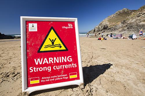 A strong currents warning sign at Chapel Porth on the Cornish coast, near St Agnes.