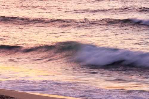 Surf on Porthmeor beach in St Ives, Cornwall, UK, at sunset.