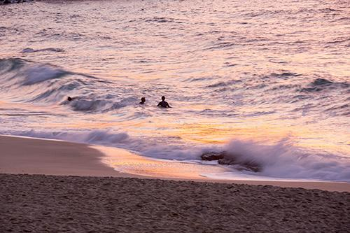 Surfers on Porthmeor beach in St Ives, Cornwall, UK, at sunset.