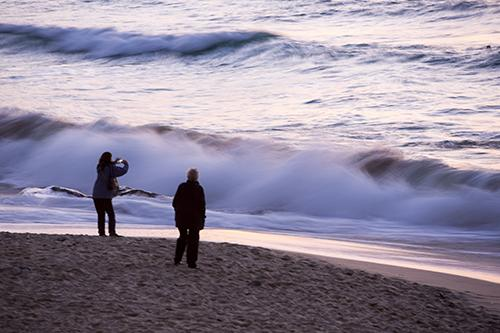 A couple at sunset on Porthmeor beach in St Ives, Cornwall, UK.