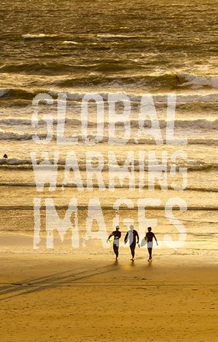 Surfers at Polzeath at sunset, Cornwall, UK.