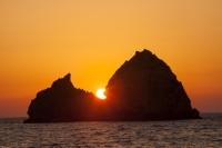 Lemnos;Greece;Limnos;Mirina;Myrina;Aegean;Meditteranean;sun;sunlight;warm;coast;sunset;evening;dusk;silhouette;tranquil;peaceful;calm;light;glow;glowing;rock;island;stack;eroded;erosion;geology;triangle;steep;rocky;shape;sharp;pointed