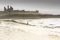 Craster;Northumberland;caost;sea;north-Sea;Dunstanburgh;Dunstanburgh-Castle;weather;storm;extreme-weather;windy;windy;hurricane;foam;wipped-up;spume;white;foamy;blowing;blown;woman;female;dog;pet;wild;wild-weather;bracing;low-pressure;coating;coated