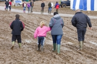 mud;muddy;field;churned-up;quagmire;wet;saturated;weather;rain;soil;trample;trampled;Lowther;Penrith;Cumbria;UK;World-Sheep-Dog-Trials;competition;event;family;child;parent;wellies;wellingtons;wellington-boots;boots;walking;pink;board-walk;struggle;struggling;footwear