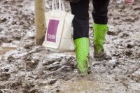 mud;muddy;field;churned-up;quagmire;wet;saturated;weather;rain;soil;trample;trampled;Lowther;Penrith;Cumbria;UK;World-Sheep-Dog-Trials;competition;event;woman;wellies;wellingtons;wellington-boots;boots;walking;pink;board-walk;struggle;struggling;footwear;carrier-bag;green;spotted;hemp-bag;shopping-bag