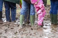 mud;muddy;field;churned-up;quagmire;wet;saturated;weather;rain;soil;trample;trampled;Lowther;Penrith;Cumbria;UK;World-Sheep-Dog-Trials;competition;event;family;child;parent;wellies;wellingtons;wellington-boots;boots;walking;pink;board-walk;struggle;struggling;footwear;pink