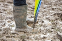 mud;muddy;field;churned-up;quagmire;wet;saturated;weather;rain;soil;trample;trampled;Lowther;Penrith;Cumbria;UK;World-Sheep-Dog-Trials;competition;event;umbrella;wellies;wellingtons;wellington-boots;boots;walking;pink;board-walk;struggle;struggling;footwear